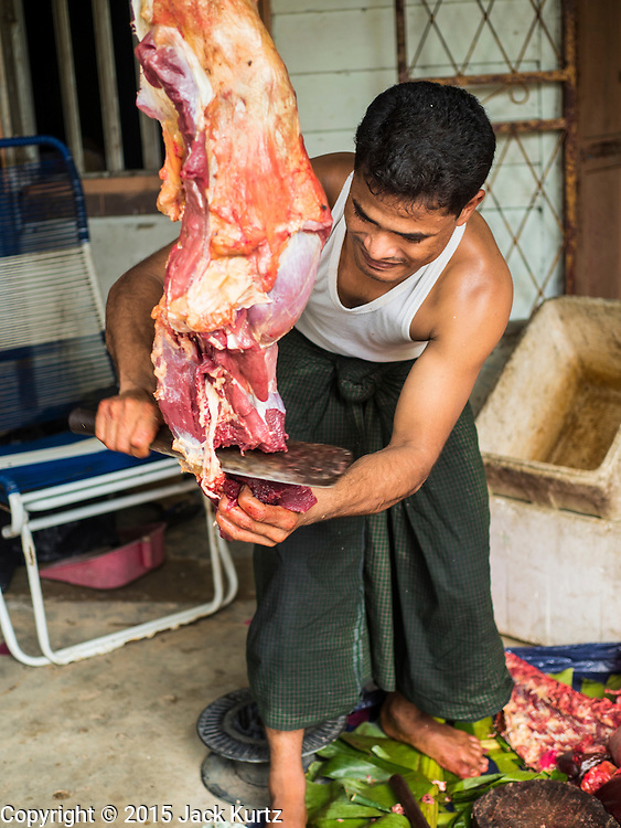 01 JUNE 2015 - KULAI, JOHORE, MALAYSIA:  A man butchers a cow sold at an informal meat shop in the Rohingya refugee community in Kulai, Malaysia. The UN says the Rohingya, a Muslim minority in western Myanmar, are the most persecuted ethnic minority in the world. The government of Myanmar insists the Rohingya are illegal immigrants from Bangladesh and has refused to grant them citizenship. Most of the Rohingya in Myanmar have been confined to Internal Displaced Persons camp in Rakhine state, bordering Bangladesh. Thousands of Rohingya have fled Myanmar and settled in Malaysia. Most fled on small fishing trawlers. There are about 1,500 Rohingya in the town of Kulai, in the Malaysian state of Johore. Only about 500 of them have been granted official refugee status by the UN High Commissioner for Refugees. The rest live under the radar, relying on gifts from their community and taking menial jobs to make ends meet. They face harassment from Malaysian police who, the Rohingya say, extort bribes from them.       PHOTO BY JACK KURTZ