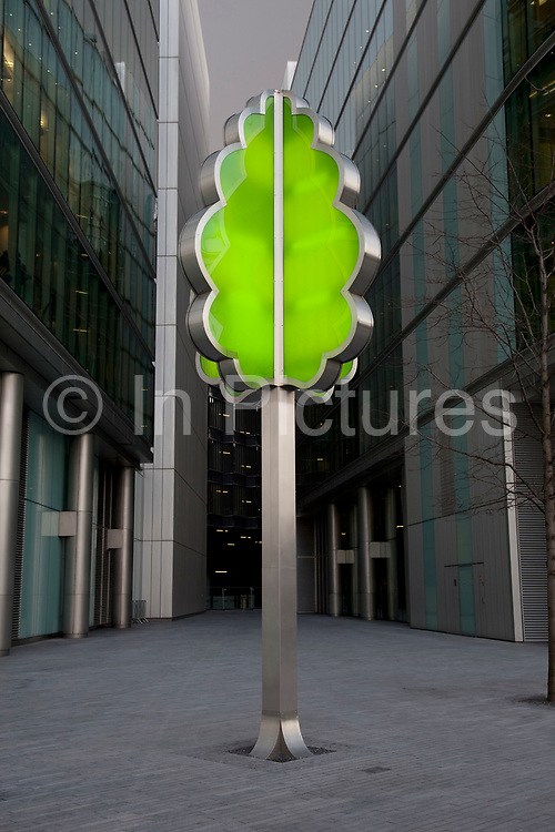 Tree sculpture made from steel and a green light box outside office buildings at More London.