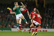 Luke Fitzgerald of Ireland jumps for a high ball with Matt Evans of Canada. Rugby World Cup 2015 pool match, Ireland v Canada at the Millennium Stadium in Cardiff, South Wales  on Saturday 19th September 2015.<br /> pic by  Andrew Orchard, Andrew Orchard sports photography.