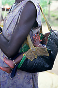 A refugee Dinka woman from South Sudan with her baby in a sling made from a recycled sack. Ikafe refugee camp, Arua, Uganda. The famine in Sudan in 1998 was a humanitarian disaster caused mainly by human rights abuses, as well as drought and the failure of the international community to react to the famine risk with adequate speed. The worst affected area was Bahr El Ghazal in southwestern Sudan. In this region over 70,000 people died during the famine.