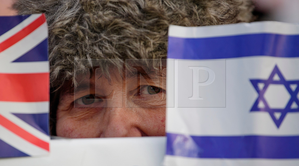 © Licensed to London News Pictures. 06/02/2017. London, UK. A woman looks between the flags of Israel and Great Britain during a pro Israel demonstration at the gates to Downing Street in London ahead of a meeting between Israeli Prime Minister Benjamin Netanyahu and British Prime Minister Theresa May in Downing Street. Photo credit: Ben Cawthra/LNP