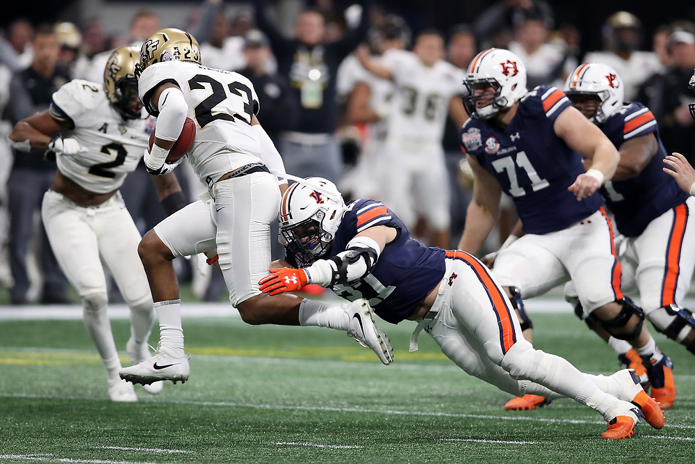 UCF Knights defensive back Tre Neal (23) is tackled by Auburn Tigers running back C.J. Tolbert (37) during the 2018 Chick-fil-A Peach Bowl NCAA football game on Monday, January 1, 2018 in Atlanta. (Jason Parkhurst / Abell Images for the Chick-fil-A Peach Bowl)