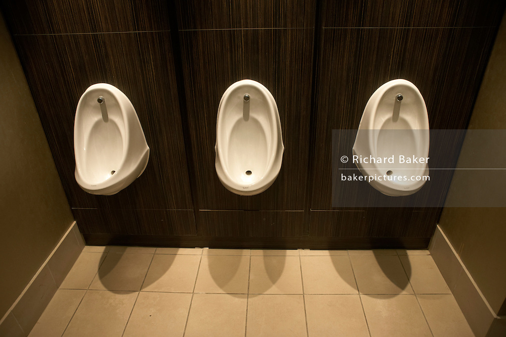 Three clean office urinal toilets fixed to dark wooden pannelling in Borough, Southwark, London.