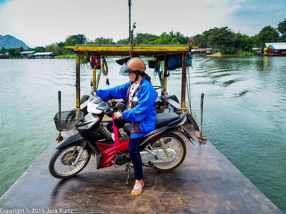 """09 JANUARY 2019 - KANCHANABURI, THAILAND: A passenger on the small ferry that goes across the River Kwai. The ferry goes across the River Kwai downriver from downtown Kanchanaburi, the site of the famous """"Bridge on the River Kwai."""" Small ferries like this, once common on Thai river crossings, are disappearing because Thailand has dramatically improved its infrastructure since this ferry started operating about 50 years ago. The ferry operator said his grandfather started the ferry, with a small raft he would pole across the river, in the late 1960s. Now his family has a metal boat with an inboard engine. There are large vehicle bridges across the river about 5 miles north and south of this ferry crossing, but for people in rural communities on the west side of the river the ferry is still the most convenient way to cross the river.      PHOTO BY JACK KURTZ"""