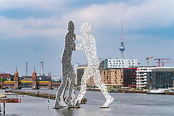 Skyline of Berlin across River Spree with large sculpture Molecule Man in Berlin Germany