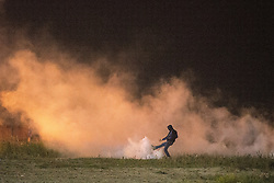 "© Licensed to London News Pictures . 23/10/2016 . Calais , France . A man kicks a tear gas canister , fired by riot police , at the Calais migrant camp known as "" The Jungle "" , in Northern France , on the evening before the start of the eviction and destruction of the camp . Photo credit: Joel Goodman/LNP"