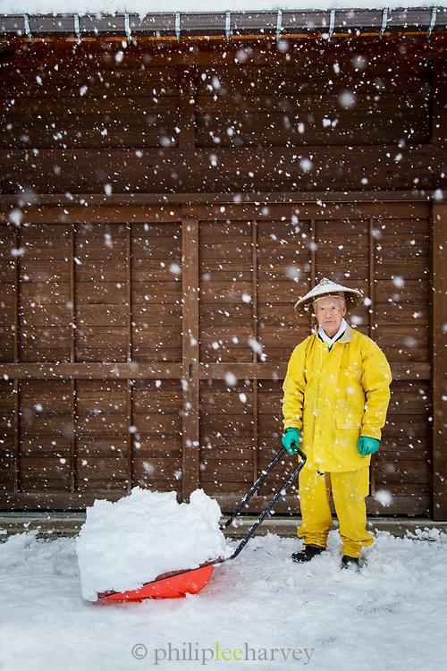 Man shoveling snow by his house, Shirakawa-go, Japan