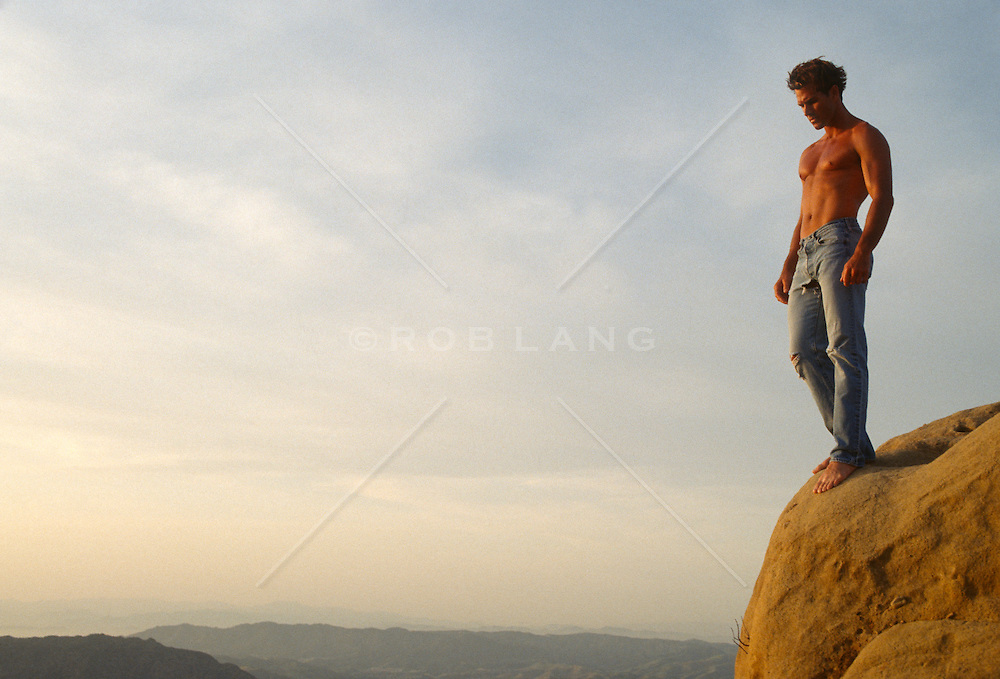 Shirtless man standing on the edge of a cliff in California