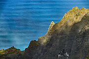 See Kalalau Valley cliffs & Pacific Ocean from Pihea Trail, Na Pali Coast, Kauai, Hawaii, USA. The potholed Pihea Trail traverses a spectacular cliff edge of Na Pali-Kona Forest Reserve, overlooking the Kalalau Valley in Na Pali Coast State Park down to the Pacific Ocean, a breathtaking 4000 feet below, on the island of Kauai. Slippery wet clay makes this a challenging hike of 2.6 miles round trip with 500 feet gain to Pihea Peak. (Optionally continue past Pihea Peak to Alaka'i Swamp Trail.) Pihea Trail begins at Pu'u O Kila Lookout at the end of the road in Koke'e State Park.