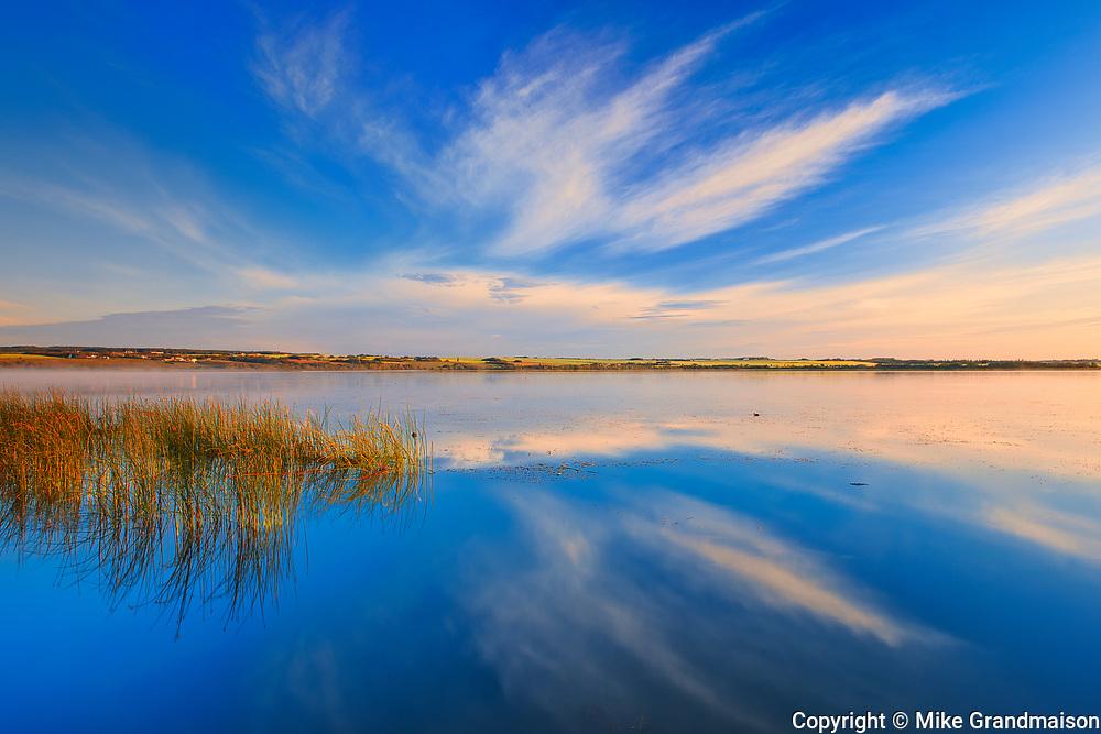 Clouds reflected in Saskatoon Lake at sunsrise<br />Saskatoon Island Provincial Park<br />Saskatchewan<br />Canada