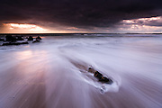 Waves pushing shorewards from the Irish Sea, at Rhosneigr, West Anglesey, at sunset with rich colors in the sky and splashes of water and movement of tide