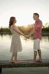 Mature couple standing with holding hands on pier at lake during sunset, Bavaria, Germany
