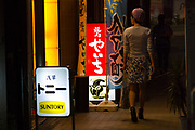 A woman walks in the street at night in Asakusa, Tokyo, Japan. Sunday May 21st 2017 .