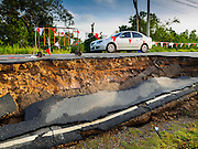 14 JULY 2015 - THAILAND: A car is driven along a collapsed roadbed in Ayutthaya province. The drought that has crippled agriculture in central Thailand is now impacting residential areas near Bangkok. The Thai government is reporting that more than 250,000 homes in the provinces surrounding Bangkok have had their domestic water cut because the canals that supply water to local treatment plants were too low to feed the plants. Local government agencies and the Thai army are trucking water to impacted communities and homes. Roads in the area have started collapsing because of subsidence caused by the retreating waters. Central Thailand is contending with drought. By one estimate, about 80 percent of Thailand's agricultural land is in drought like conditions and farmers have been told to stop planting new acreage of rice, the area's principal cash crop.       PHOTO BY JACK KURTZ