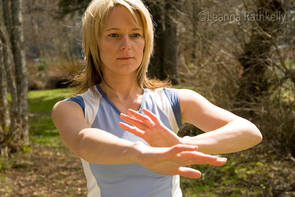 A woman does tai chi moves outdoors on a spring day in Whistler, BC Canada