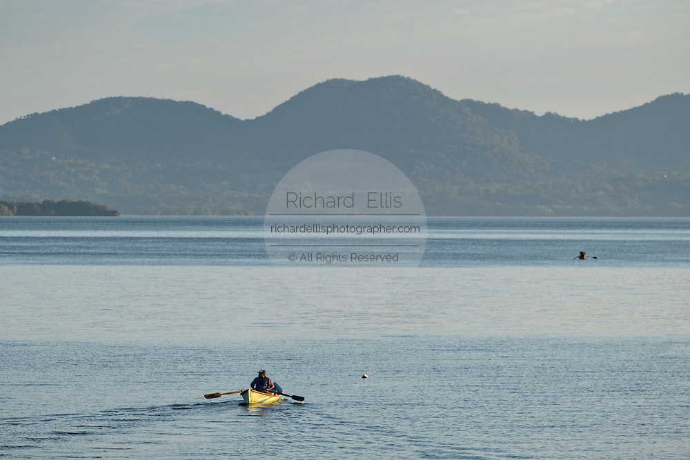A fisherman rows a traditional boat around the Lake Catemaco, Veracruz, Mexico. The lagoon which flows into the Gulf of Mexico is one of the best preserved coastal wetlands and mangroves forests in Mexico and part of the Los Tuxtlas biosphere reserve.