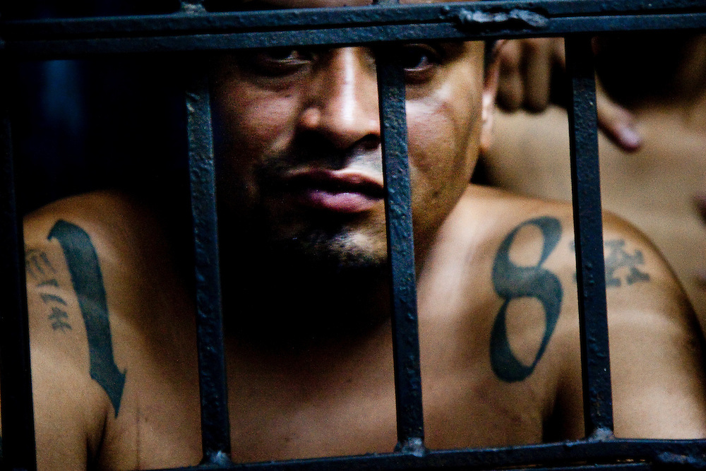 Eduardo looks  out of the 18th Street jail cell  in the Ilopango barrio, one of San Salvador's most violent.  This is his  34th birthday and  he says the 10th time he has  been put in jail without charges.  He was deported from the states in 1994 and served 4 years in 2000 for armed robbery.  He says he is trying to move on from the Maras to raise his daughter, but it is difficult.  He was put in jail for being for other members of 18th street.  Even if a Mara stops doing activities with gangs, the relationships made in the gang last for ever.