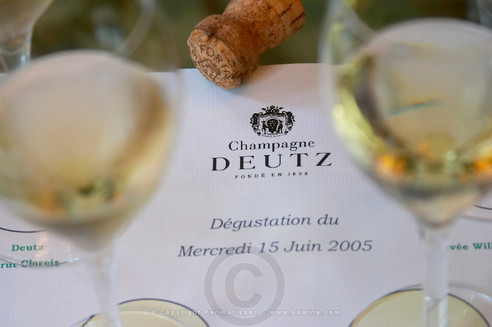 Glasses of champagne set on a white background for a tasting of the range of wines and a cork at Champagne Deutz in Ay, Vallee de la Marne, Champagne, Marne, Ardennes, France, low light grainy grain