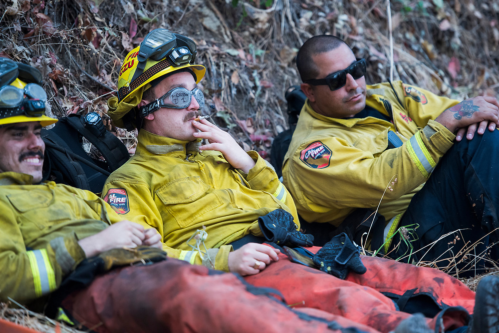 CalFire firefighters take a break while fighting the Glass Fire along Old Lawley Toll Road near Calistoga California on Oct. burns on Oct. 2, 2020.