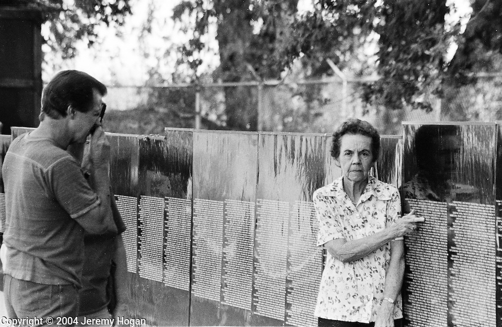 A woman points to the name of her son who was killed while serving the United States during the Vietnam War. The moving wall was making a stop in Porterville, California - Porterville had the most soldiers killed per capita of any town in America. 1989 .
