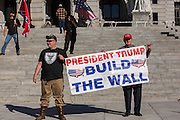 """Arthur Jones (right) holds a sign reading """"President Trump build the wall"""" in front of the Pennsylvania State Capitol during the National Socialist Movement fall political rally in November of 2016."""