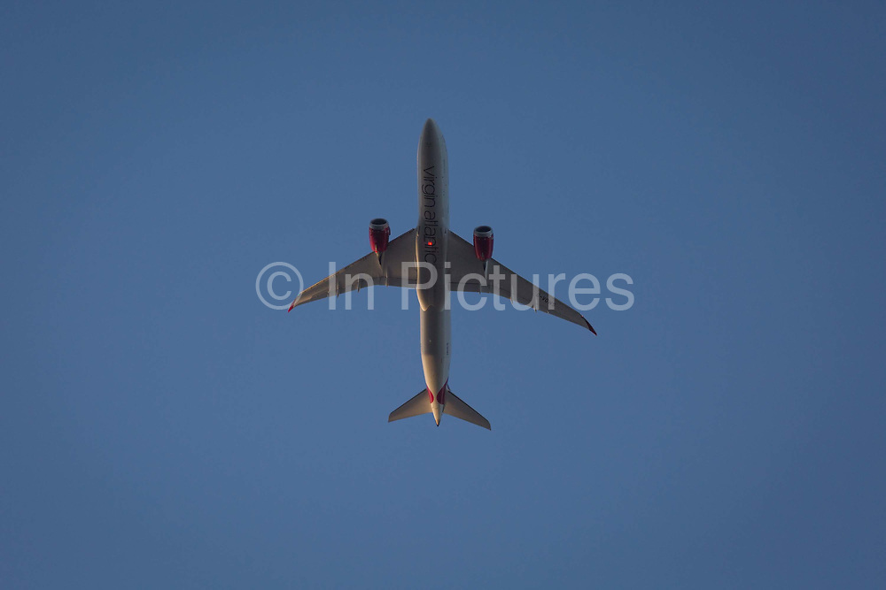 A Boeing 787-9 jet airliner with Virgin Atlantic G-VOWS flies overhead in blue skies on its flight-path into London Heathrow airport, on 10th August 2018, in London, England.