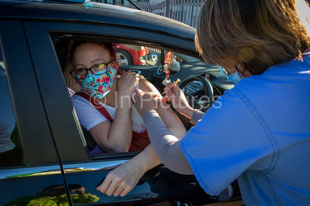 A patient receives their first dose of the COVID-19 AstraZeneca Oxford vaccine in their arm while attending the drive through vaccination centre in the car park of Folkestone council offices on Saturday the 27th of February 2021, Folkestone, Kent, United Kingdom.