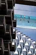 With the architecture of the US Embassy below, swimmers enjoy the waters of the Sky Pool, a 25 metres-long transparent water pool bridging two 10-storey residential towers 35 metres above the ground, the largest freestanding acrylic pool structure in the world at EcoWorld Ballymore's new Embassy Gardens development in Nine Elms, on 3rd June 2021, in London, England.