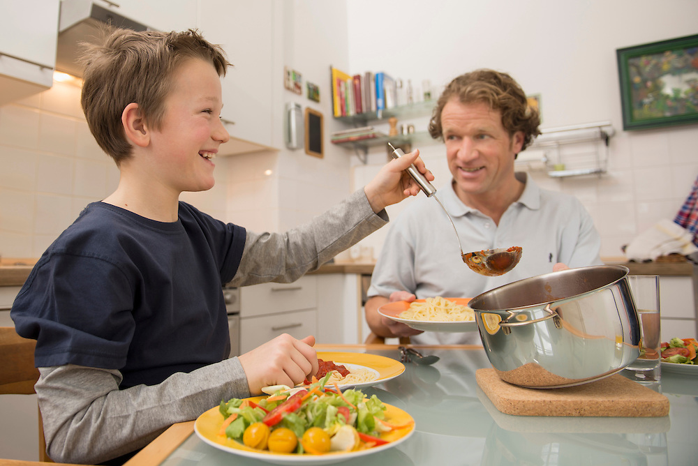 Father and son eating spaghetti and salad in kitchen