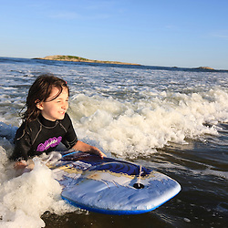 A girl (age 8) boogie boarding at Popham Beach State Park in Phippsburg, Maine.