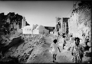 Children playing in front of the hilltop mosque at largely abandoned Berber village of Chenini, Tunisia.  This mountain refuge is largely uninhabited as the plains have grown safer from bandits and the difficulty of bringing water up its steep slopes.