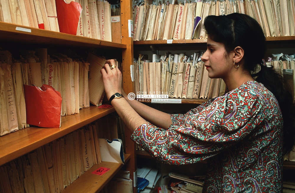 Female receptionist filing patient's medical records in doctor's surgery,
