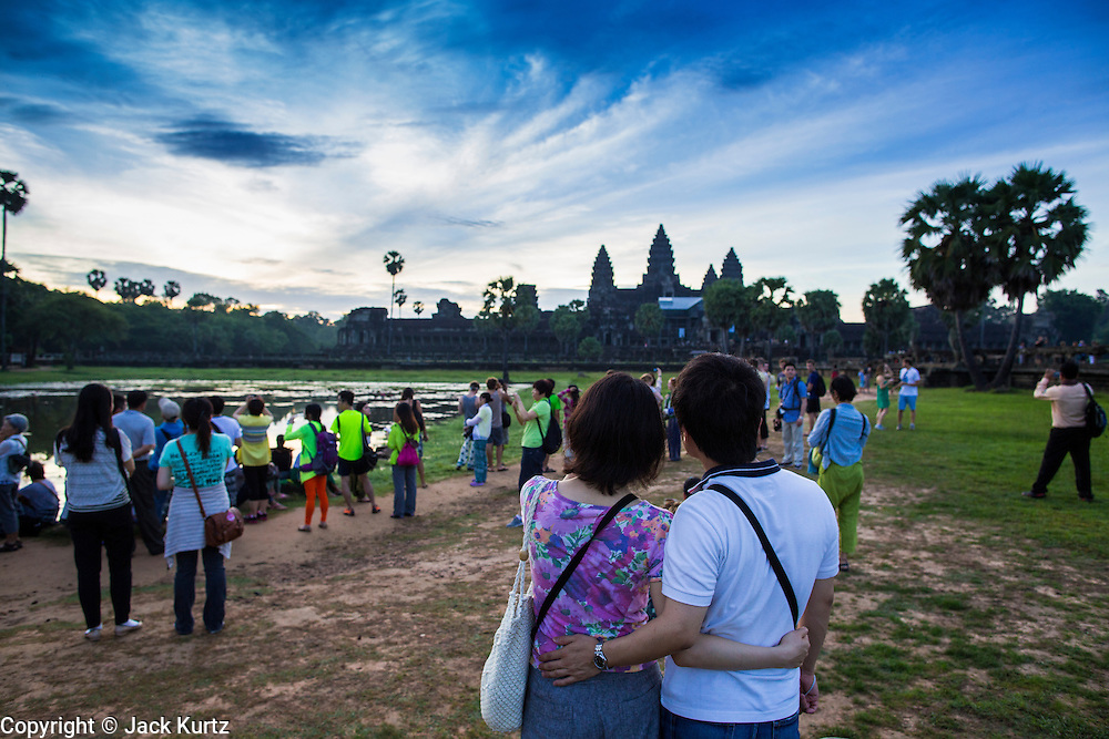 """02 JULY 2013 - ANGKOR WAT, SIEM REAP, SIEM REAP, CAMBODIA:  Tourists watch the sunrise at Angkor Wat. Angkor Wat is the largest temple complex in the world. The temple was built by the Khmer King Suryavarman II in the early 12th century in Yasodharapura (present-day Angkor), the capital of the Khmer Empire, as his state temple and eventual mausoleum. Angkor Wat was dedicated to Vishnu. It is the best-preserved temple at the site, and has remained a religious centre since its foundation– first Hindu, then Buddhist. The temple is at the top of the high classical style of Khmer architecture. It is a symbol of Cambodia, appearing on the national flag, and it is the country's prime attraction for visitors. The temple is admired for the architecture, the extensive bas-reliefs, and for the numerous devatas adorning its walls. The modern name, Angkor Wat, means """"Temple City"""" or """"City of Temples"""" in Khmer; Angkor, meaning """"city"""" or """"capital city"""", is a vernacular form of the word nokor, which comes from the Sanskrit word nagara. Wat is the Khmer word for """"temple grounds"""", derived from the Pali word """"vatta."""" Prior to this time the temple was known as Preah Pisnulok, after the posthumous title of its founder. It is also the name of complex of temples, which includes Bayon and Preah Khan, in the vicinity. It is by far the most visited tourist attraction in Cambodia. More than half of all tourists to Cambodia visit Angkor.         PHOTO BY JACK KURTZ"""