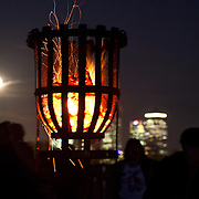Canary Wharf, the full moona and on-lookers behing the burning beacon. One of 4000 beacons lit across the word was lit in Tower Hamlets, London by Mayor Rahman. Tower Hamlet is one of the UK's poorest councils and also home to the financial district Canary Wharf on the Isle of Dogs.  Celebrations in London, UK for Queen Elizabeth II Diamond Jubilee. 60 years as monarch in Britain. Celebrations in London, UK for Queen Elizabeth II Diamond Jubilee.