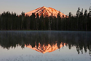 Lassen Peak, a 10,462 foot (3,189 meter) volcano in northern California, is reflected in the calm waters of Summit Lake at sunrise. Lassen Peak is the southernmost volcano in the Cascade Range and last erupted from 1914-1917.