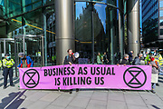 Members of Extinction Rebellion Youth Cambridge hold a banner 'Business as usual is killing us' as they blocked the road outside Baringa Partners building in London on Thursday, Sept 10, 2020 - in an attempt to highlight the involvement of Schlumberger Limited in what they call 'ecocide'. Schlumberger is an oilfield services company working in more than 120 countries and has four principal executive offices located in Paris, Houston, London, and The Hague. An article at the Guardian suggests that it's ubiquitous in fossil fuel operations across the world, has more staff than Google, turns over more than Goldman Sachs, and is worth more than McDonald's – yet you won't have heard of it. XR Youth of Cambridge said that the British government gave Schlumberger a no-strings-attached £150 million bailout loan as it was laying off a fifth of its global workforce. Another activist added: 'Schlumberger is hiding in plain sight here in Westminster. Every day, hundreds of people walk past this building with no idea that they're on the doorstep of a climate crime scene.'<br /> Environmental nonviolent activists group Extinction Rebellion enters its 10th and final day of continuous ten days protests to disrupt political institutions throughout peaceful actions swarming central London into a standoff, demanding that central government obeys and delivers Climate Emergency bill. (VXP Photo/ Vudi Xhymshiti)