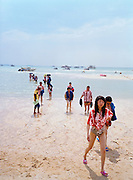 A group of Korean tourists in matching shirts wade ashore on Pattaya beach after a boat trip.