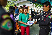 """17 JULY 2014 - BANGKOK, THAILAND: Thai immigration police check the temporary ID cards of undocumented Cambodian workers at the temporary """"one stop service center"""" in the Bangkok Youth Center in central Bangkok. Thai immigration officials have opened several temporary """"one stop service centers"""" in Bangkok to register undocumented immigrants and issue them temporary ID cards and work permits. The temporary centers will be open until August 14.    PHOTO BY JACK KURTZ"""
