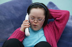 Downs Syndrome teenage girl using the telephone,