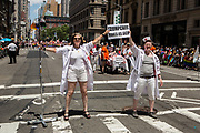 """New York, NY - 25 June 2017. New York City Heritage of Pride March filled Fifth Avenue for hours with groups from the LGBT community and it's supporters. Two women dressed as nurses, one with an IV pole, carrying a sign that reads """"Trumpcare makes us sick."""""""
