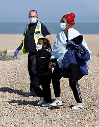 © Licensed to London News Pictures. 22/09/2021. Dungeness, UK. Mother and daughter migrants are escorted ashore buy a Border Force Officer at Dungeness in Kent after being rescued by the RNLI as they crossed the English Channel. Hundreds of migrants have made the crossing in the calm weather this week. Photo credit: Sean Aidan/LNP