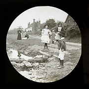 Magic lantern slide of mothers with children outside playing by a stream in a village rural location, UK circa 1900