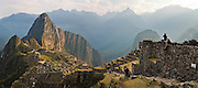 Tourists, sitting on the terraces overlooking the main ruins, enjoy the sunrise at the spectacular archeological site of Machu Picchu, Peru.