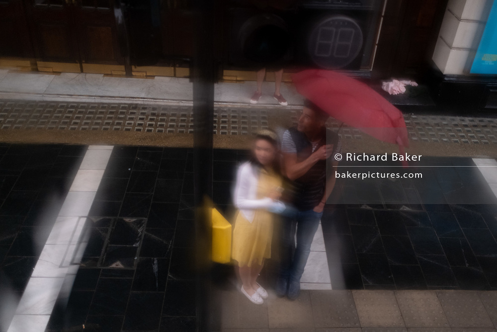 Seen through a wet bus window, a man holds a red umbrella over himself alongside a woman during summer rains on Shaftesbury Avenue, on 27th August 2020, in London, England.
