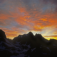 A sunset lights clouds over Mounts Winchell and Aggasiz in California's Sierra Nevada. Below is the Palisade Glacier.