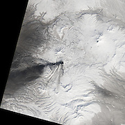 """Five Volcanoes Erupting at Once<br /> <br /> Remote. Cold. Rugged. Those three adjectives capture the essence of Russia's Kamchatka Peninsula. Another word—perhaps more applicable than anywhere else on Earth—is """"fiery.""""<br /> Of the roughly 1,550 volcanoes that have erupted in the recent geologic past, 113 are found on Kamchatka. Forty Kamchatkan volcanoes are """"active,"""" either erupting now or capable of erupting on short notice. The Operational Land Imager (OLI) on Landsat 8 captured activity at five of them during a single satellite pass on April 14, 2014.<br /> From geographic north to south (and top to bottom on this page), the volcanoes are Shiveluch, Klyuchevskaya, Bezymianny, Kizimen, and Karymsky. The tallest of the group is Klyuchevskaya, a stratovolcano with a steep, symmetrical cone that reaches 4,750 meters (15,580 feet) above sea level. The most active is Karymsky, a 1,536-meter (5,039-foot) peak that has erupted regularly since 1996.<br /> Plate tectonics is responsible for the many volcanoes on Kamchatka Peninsula. The Pacific Plate is slowly colliding with and sliding beneath the Okhotsk Plate. As rock from the Pacific Plate descends and encounters higher pressures and temperatures, it melts into magma. Over time, magma accumulates and migrates up toward the surface, causing volcanic eruptions.<br /> Long before the discovery of plate tectonics, Kamchatka's many volcanoes and eruptions were woven into a rich tapestry of myths and creation stories. According to Koryak folklore, the raven-like deity Kutkh created Kamchatka by dropping a giant feather on the Pacific Ocean. Each of the first generation of men became one of Kamchatka's mountains at death; many of these mountains became volcanic because the men's hearts burned so passionately for a beautiful woman that Kutkh had also created near the beginning of time.<br /> Photo Shows Karymsky <br /> ©Earth Observatory/Exclusivepix"""