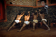 Participants stretch their muscles before a contest of Kalarippayat, a game of combat skills with curved wooden weapons, Cochin, Kerala, India