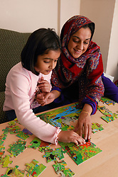 Single parent helping her young daughter do a jigsaw puzzle,