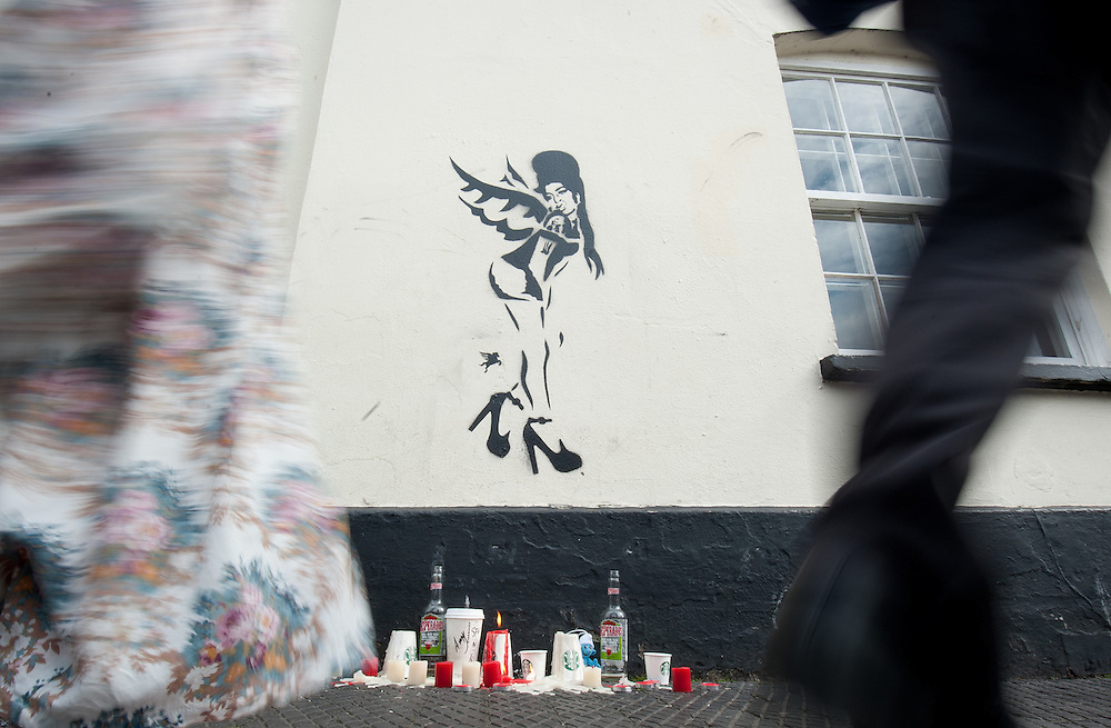 A Banksy style piece of graffiti has popped up on Camden Lock with candles underneath paying tribute  to signer Amy Winehouse who was found dead in her flat on July 23 in London on July 25th 2011...Tributes have been paid to singer Amy Winehouse, 27, has been found dead at her north London home on July 23rd 2011...A Metropolitan Police spokesman said the cause of Winehouse's death was as yet unexplained...The Brit and Grammy award-winner had struggled with drink and drug addiction and had recently spent time in rehab....