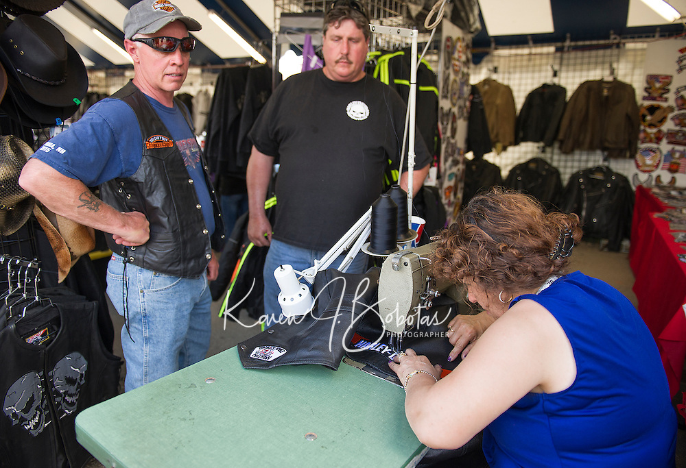 Mike Larrabee and Jeff Woodbury from Maine have new patches sewn on their leather vests with Maria Bernardo.  Bernardo has been sewing on patches at Bike Week for 30 years.  (Karen Bobotas/for the Laconia Daily Sun)